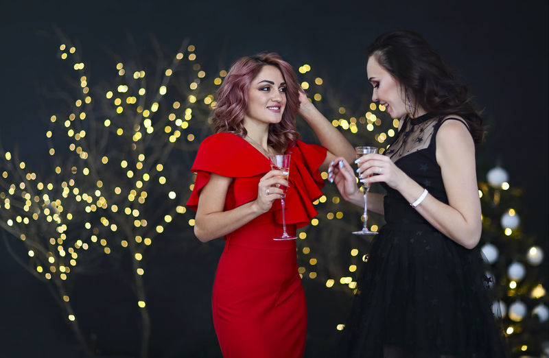 Beautiful women wearing gown holding drinks standing outdoors at night