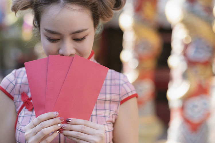 Close-up of woman holding red envelopes