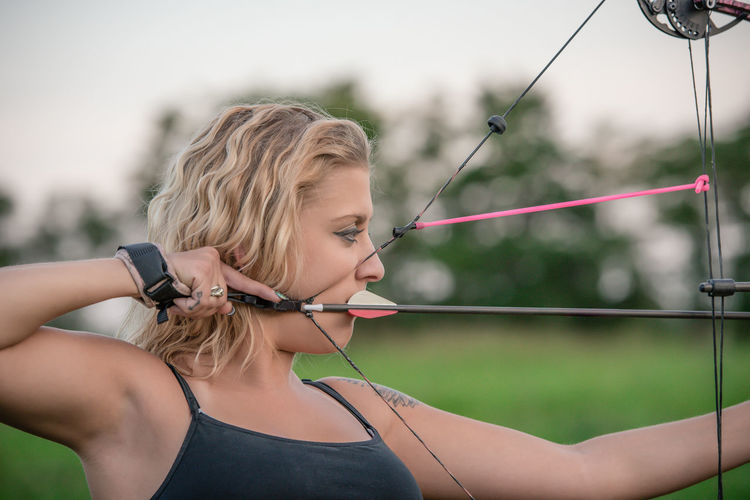 Close-Up Of Young Woman Aiming Bow At Park