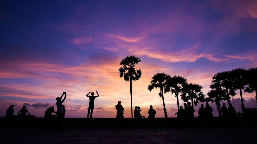 Silhouette people and palm trees against dramatic sky during sunset
