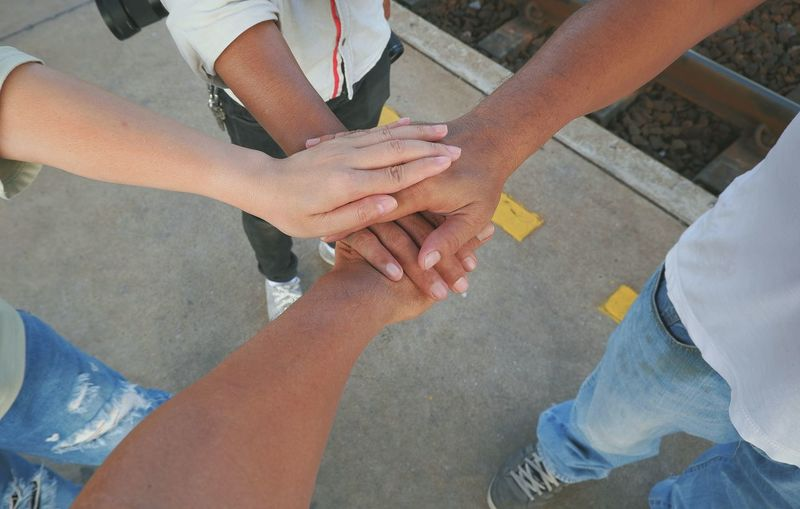 Group of traveler friends putting and join their hands together on train platform, Travelers teem with stacked of hands showing close friends unity group on friendship in travel concept Train Station Railway Platform Lifestyles Togetherness Travel Journey Concept Friendship Close Friends Group Traveler Enjoy Stacked Human Hand Volunteer Teamwork Togetherness Unity Women High Angle View Men Close-up Human Arm Body Part Agreement