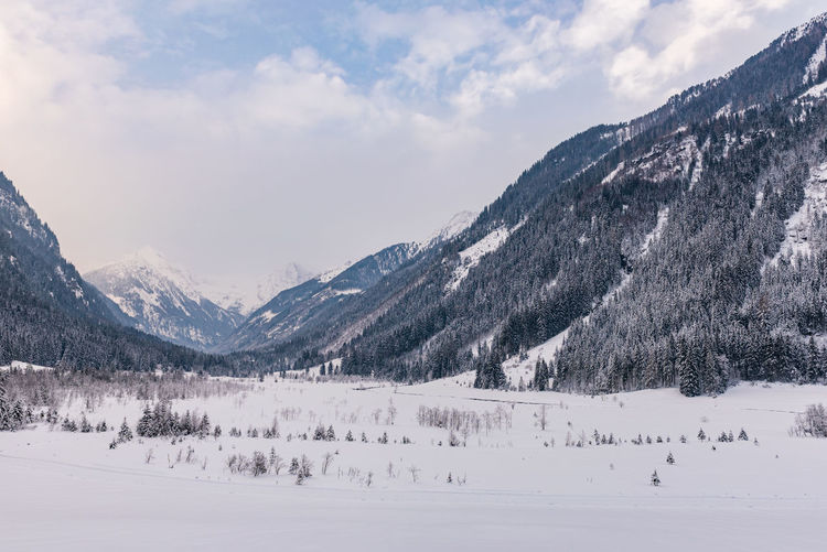 Scenic view of snowcapped mountains valley against sky. austrian apls in winter.