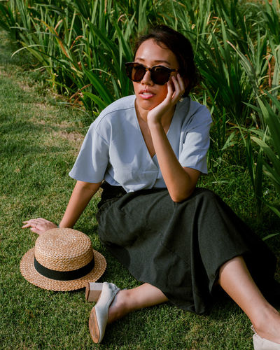Lydia Teo Grass Green Fashion Portrait Portrait Of A Woman Portrait Photography Summer Garden Sitting Light Portrait Sitting Smiling Sunglasses Full Length Happiness Grass Straw Hat Posing Hat