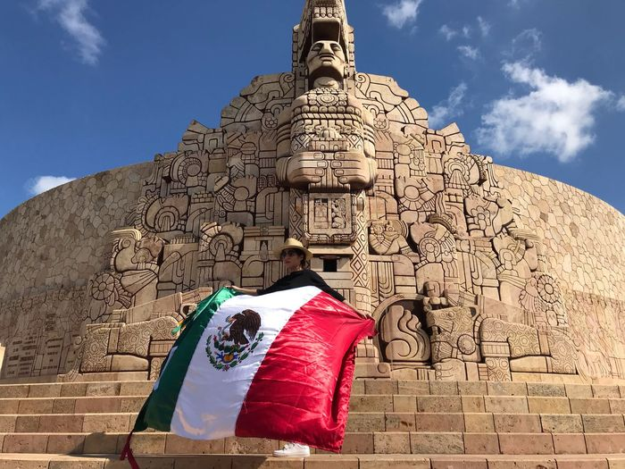 Woman holding mexican flag against historic building