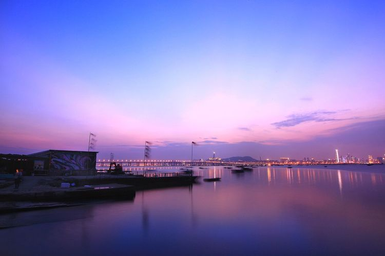 Scenic view of bay against sky at sunset