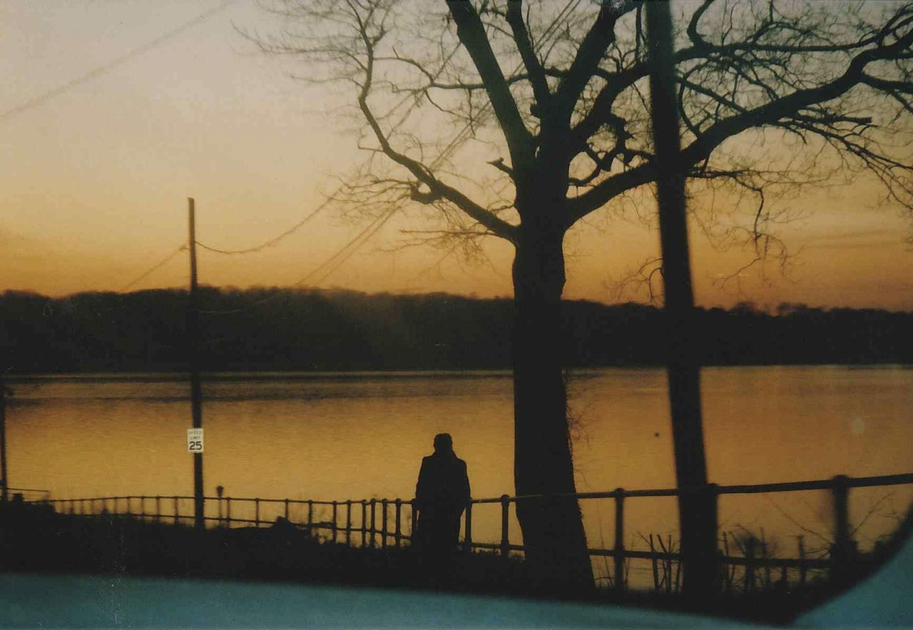 SILHOUETTE PEOPLE BY RIVER AGAINST SKY AT SUNSET