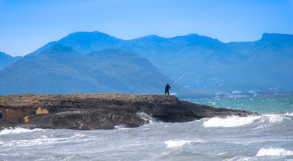 Man Fishing On Rock Formation At Sea By Mountains Against Sky
