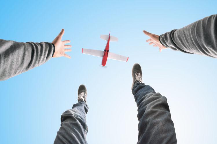 Directly below shot of man gesturing against airplane in sky