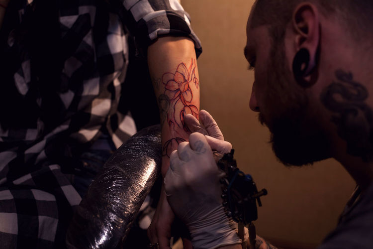 Painful procedure of getting tattoo from professional tattoo artist Real People Human Hand Indoors  Human Body Part Hand People Two People Holding Men Weapon Midsection Close-up Creativity Art And Craft Lifestyles Tattoo Occupation Artist Tattooing