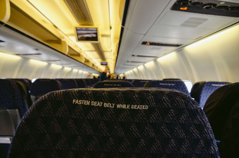 Vehicle Interior Transportation Seat Mode Of Transportation Vehicle Seat Airplane Travel Air Vehicle Text Public Transportation Airplane Seat Journey In A Row Indoors  Absence Passenger Cabin Sitting No People Communication Western Script Aisle Ceiling Cabin