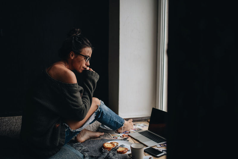 Young woman looking away while sitting at home
