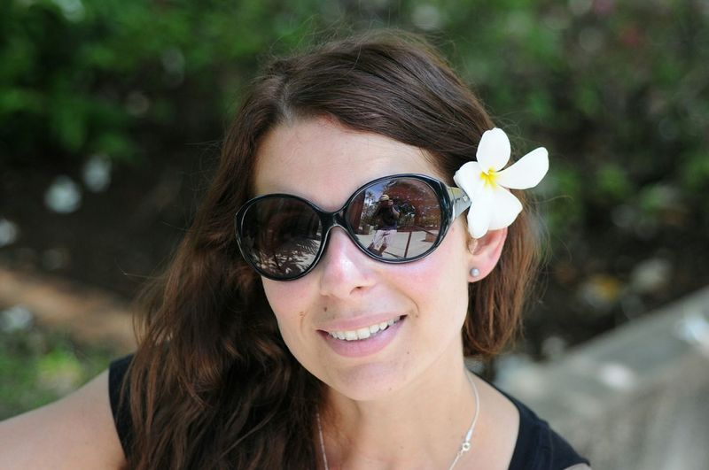 Close-up of smiling woman wearing sunglasses and flower