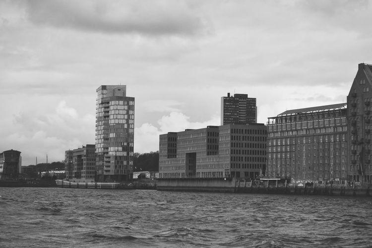 Sea by buildings against sky