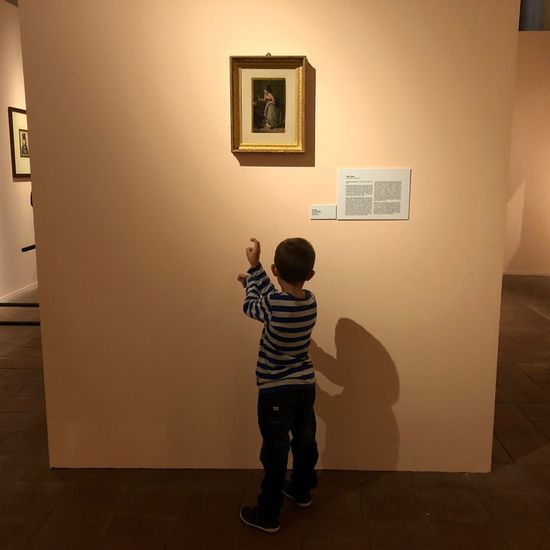 Rear view of boy standing against wall at home