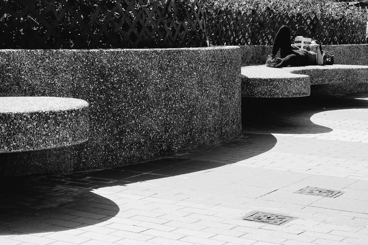 Architecture Concrete Day Footpath Full Length Leisure Activity Lifestyles Nature One Person Outdoors Paving Stone Plant Real People Relaxation Retaining Wall Shadow Sitting Stone Sunlight Water Women
