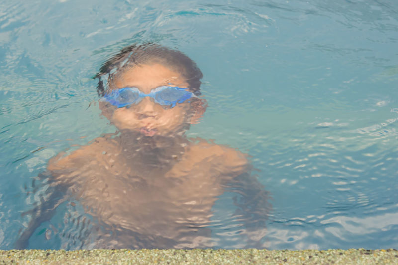 High angle view of shirtless boy swimming in pool