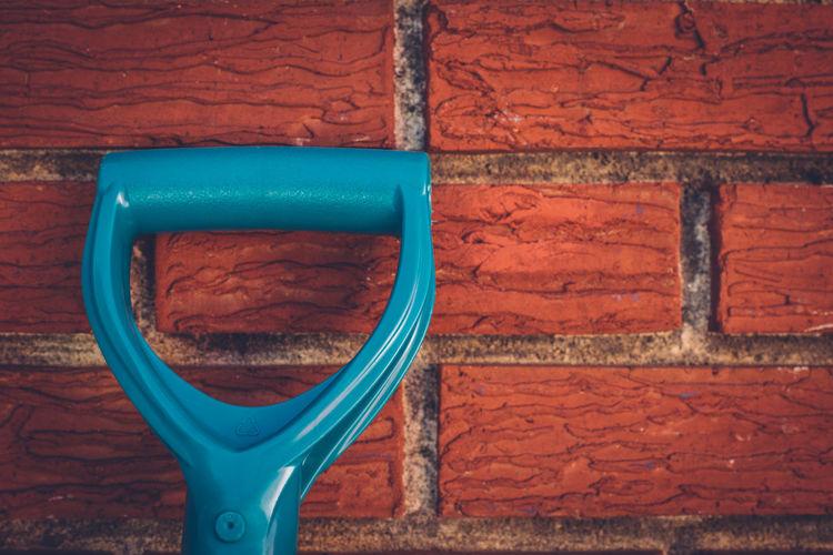 Close-up of shovel by brick wall