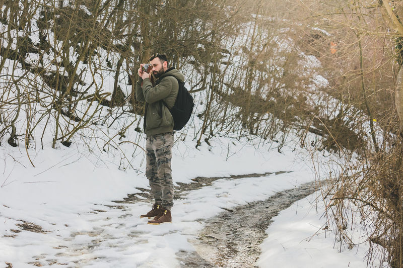 Young Man Photographing On Snow Covered Road At Forest During Winter