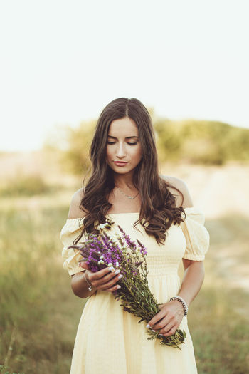 Beautiful young woman holding flower bouquet standing against plants