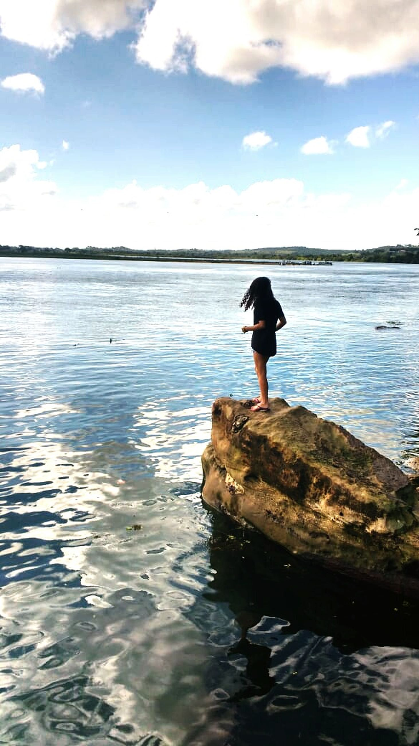 water, sky, sea, rock, real people, one person, beauty in nature, rock - object, solid, leisure activity, scenics - nature, lifestyles, cloud - sky, nature, standing, tranquility, waterfront, vacations, beach, outdoors