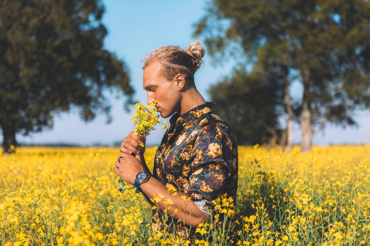 Portrait of the blond curly man. Staying in the field and sniffs a flowers. Summer time. blue sky. Copy space for advertising. People and lifestyle concept. Beauty In Nature Casual Clothing Day Field Flower Flowering Plant Freshness Growth Land Leisure Activity Lifestyles Nature One Person Outdoors Plant Real People Side View Yellow Young Adult Young Women