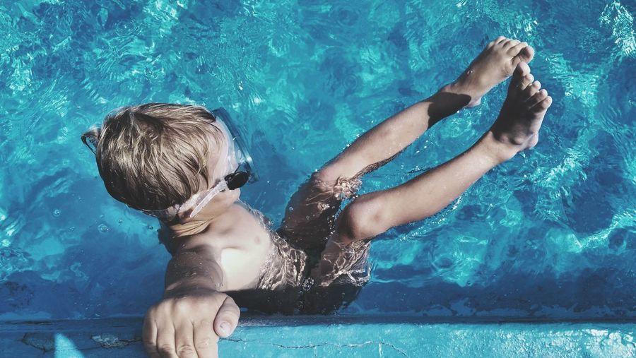 Full length of shirtless boy swimming in pool