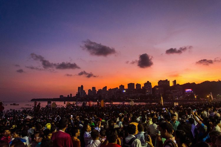 Crowd at beach against sky during sunset