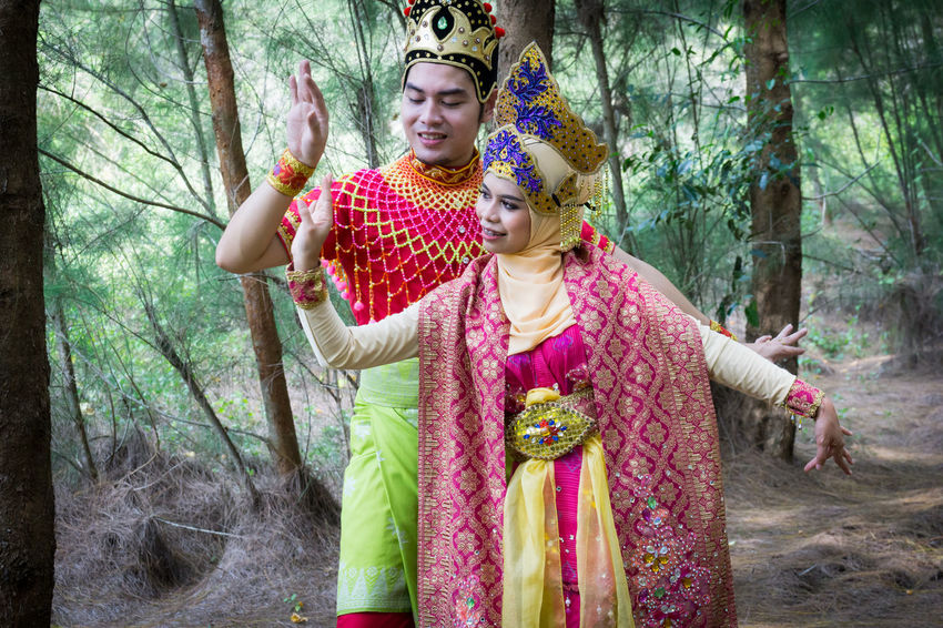 Specific to the villages of Kelantan, where the tradition originated, Mak Yong is performed mainly as entertainment or ritual purposes by couple of dancers. Adult Adults Only Bride Bridegroom Day Forest Front View Holding Mak Yong Nature Outdoors People Real People Standing Togetherness Traditional Clothing Tree Two People Young Adult Young Men Young Women