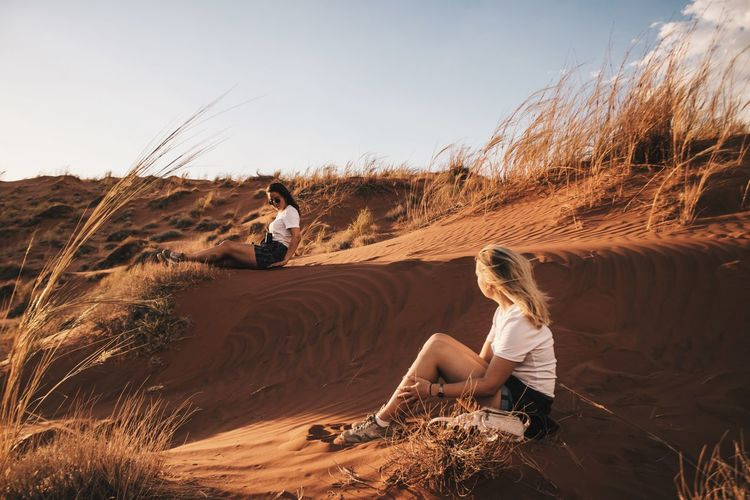 Friends sitting on desert against sky