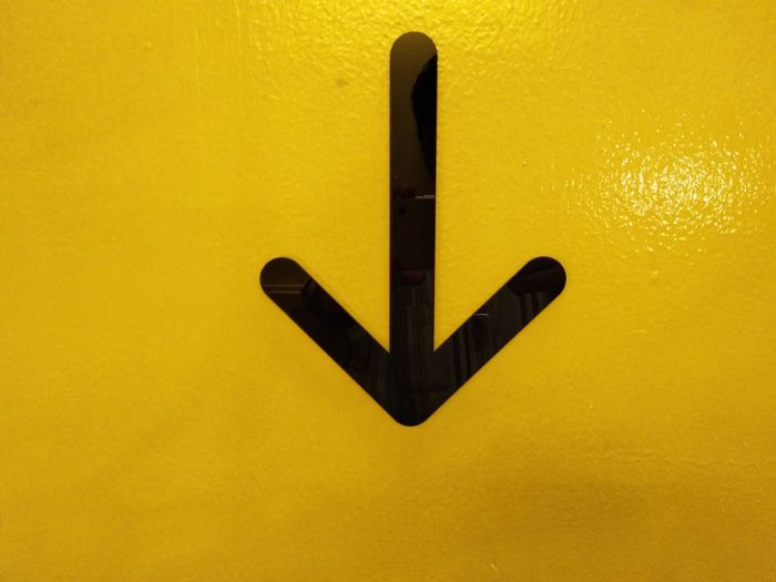 Close-up of black sign on yellow background
