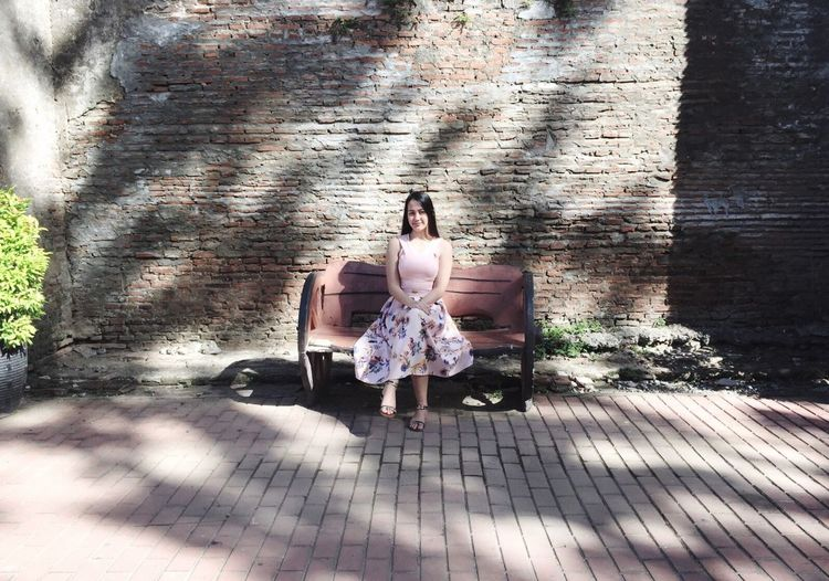 Portrait of beautiful woman sitting on bench against brick wall