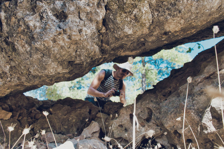 Low angle view of man seen through hole in rock