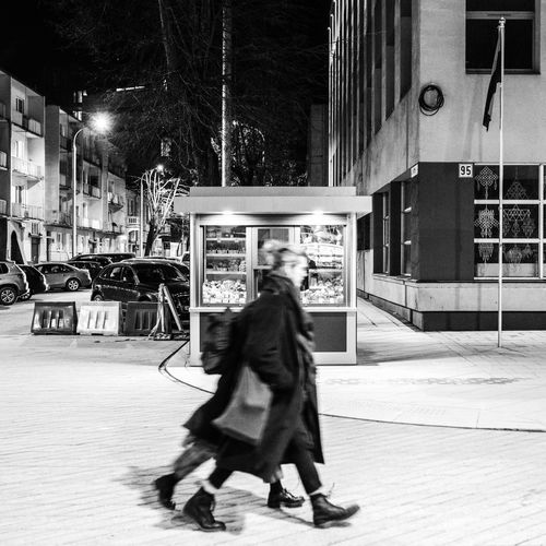 Woman walking on street in city at night
