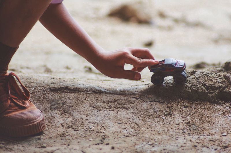 Cropped image of boy playing with toy car