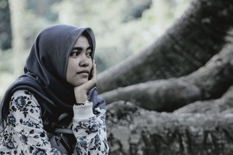 Young woman wearing hijab looking away sitting by tree trunk