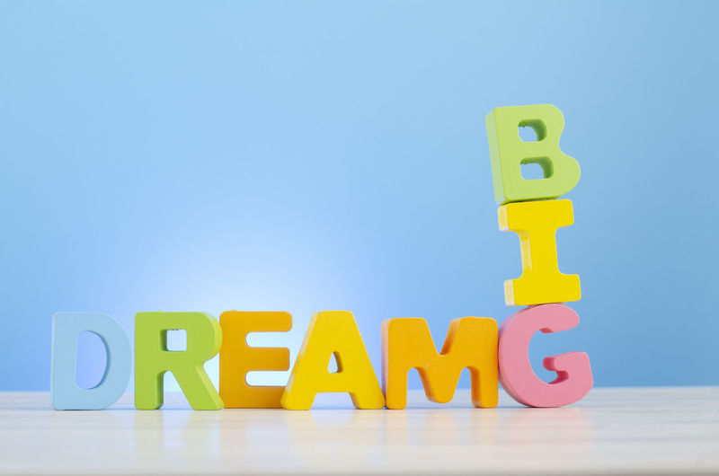 DREAM BIG word on wooden desk over blue background Capital Letter Text Communication Multi Colored Toy Block Western Script Toy Alphabet Letter Childhood Blue Indoors  Studio Shot Still Life Yellow Education Copy Space Table Learning Blue Background