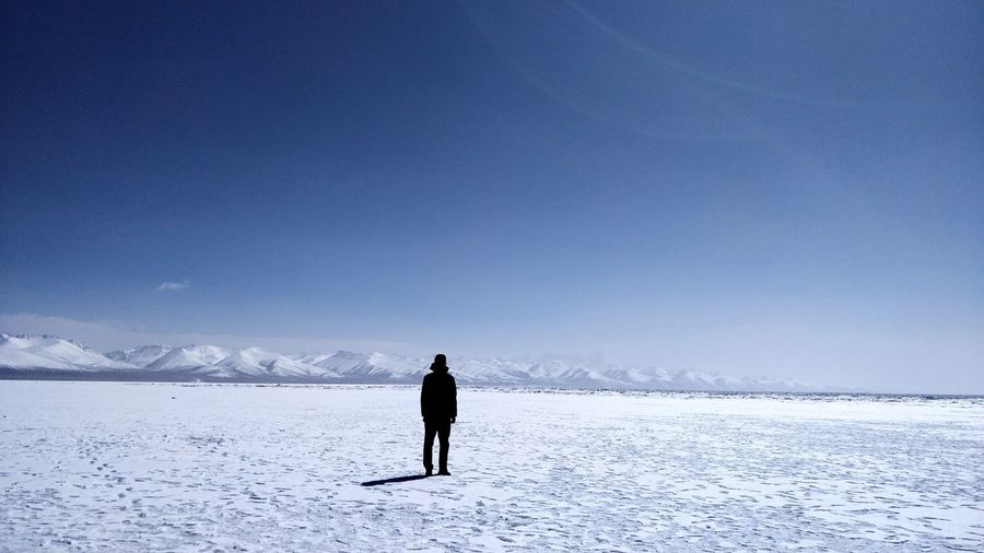 Full length of person walking on snow covered mountain against sky