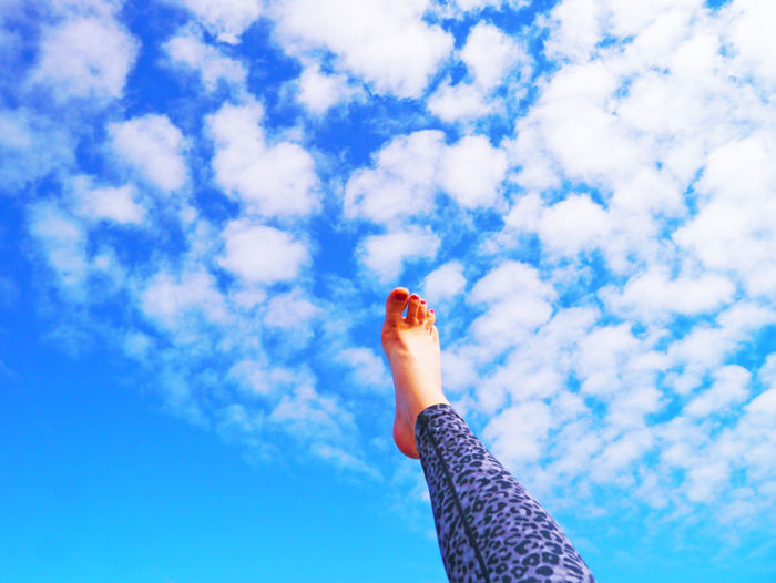 Low Section Of Woman Against Blue Sky