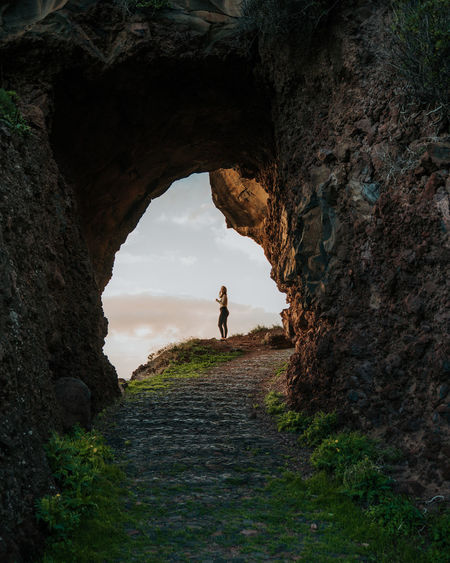 Full length of woman seen through rock formation against sky
