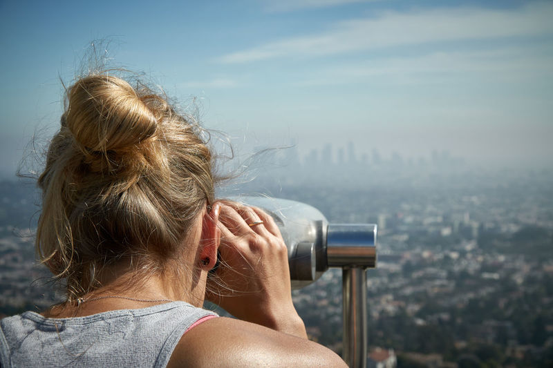 Woman looking at cityscape through coin-operated binoculars against sky