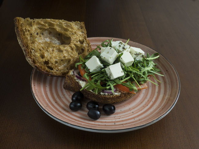 sandwich with feta cheese, tomatoes, olives, red onions and arugula Red Onions Sandwich Arugula Bread Cheese Close-up Day Feta Food Food And Drink Freshness Healthy Eating Indoors  No People Olives Plate Ready-to-eat Table Tomatoes