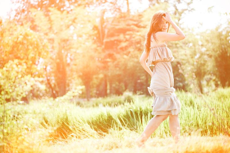 Side view portrait of woman walking on field