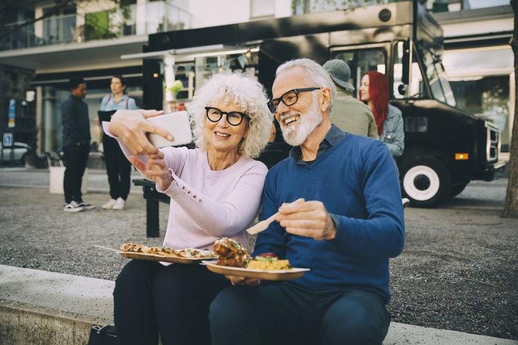 People eating food on street in city