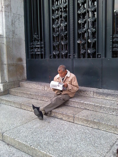 Senior man reading newspaper while sitting on steps by door