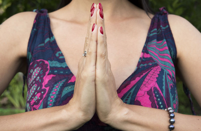Midsection of woman meditating with hands clasped