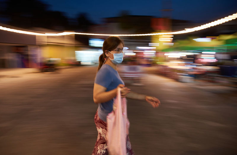 Side view of woman standing on street at night