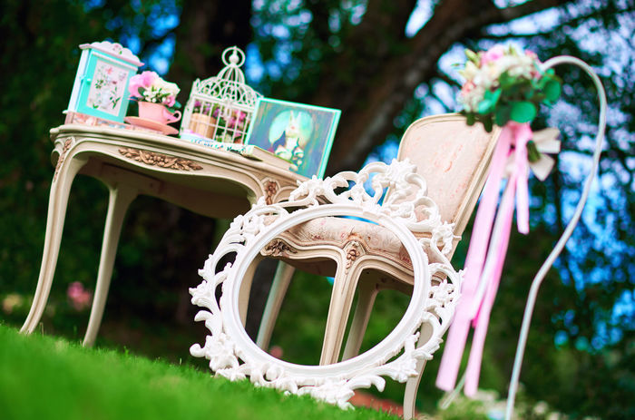 Retro styled chair, table and white carved frame. Pretty things, symbols of Alice in Wonderland Beautiful Chair Retro Summertime Sunny Vintage Style Alice In Wonderland Aliceinwonderland Beauty Bouquet Bouquet Of Flowers Carved Wood Flowers Frame Green Lawn No People Nobody Outdoors Pretty Retro Style Retro Styled Summer Sunny Day Table Vintage