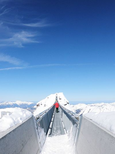 Rear view of people walking on footbridge at snow covered mountains against sky
