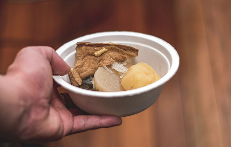 Close-up of hand holding food in bowl on table