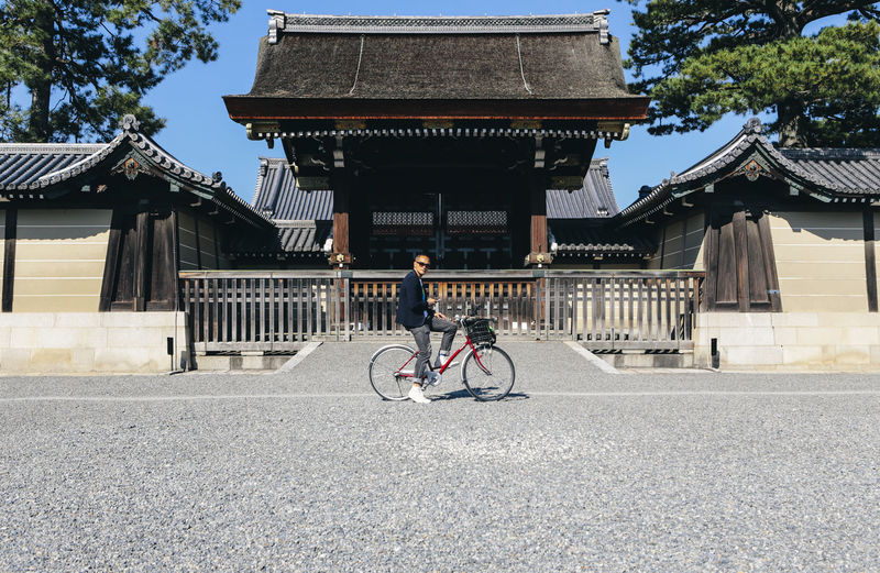 A tourist stops in front of the Imperial Palace Gate. The photo shows a tourist on his bicycle taking a break, looking at his cellphone for directions. Emperor Palace Gate Imperial Imperial Palace Japan Man Architecture Bicycle Building Building Exterior Built Structure Day Kyoto Kyoto,japan Land Vehicle Lifestyles Mode Of Transportation One Person Outdoors Real People Ride Riding Transportation Travel